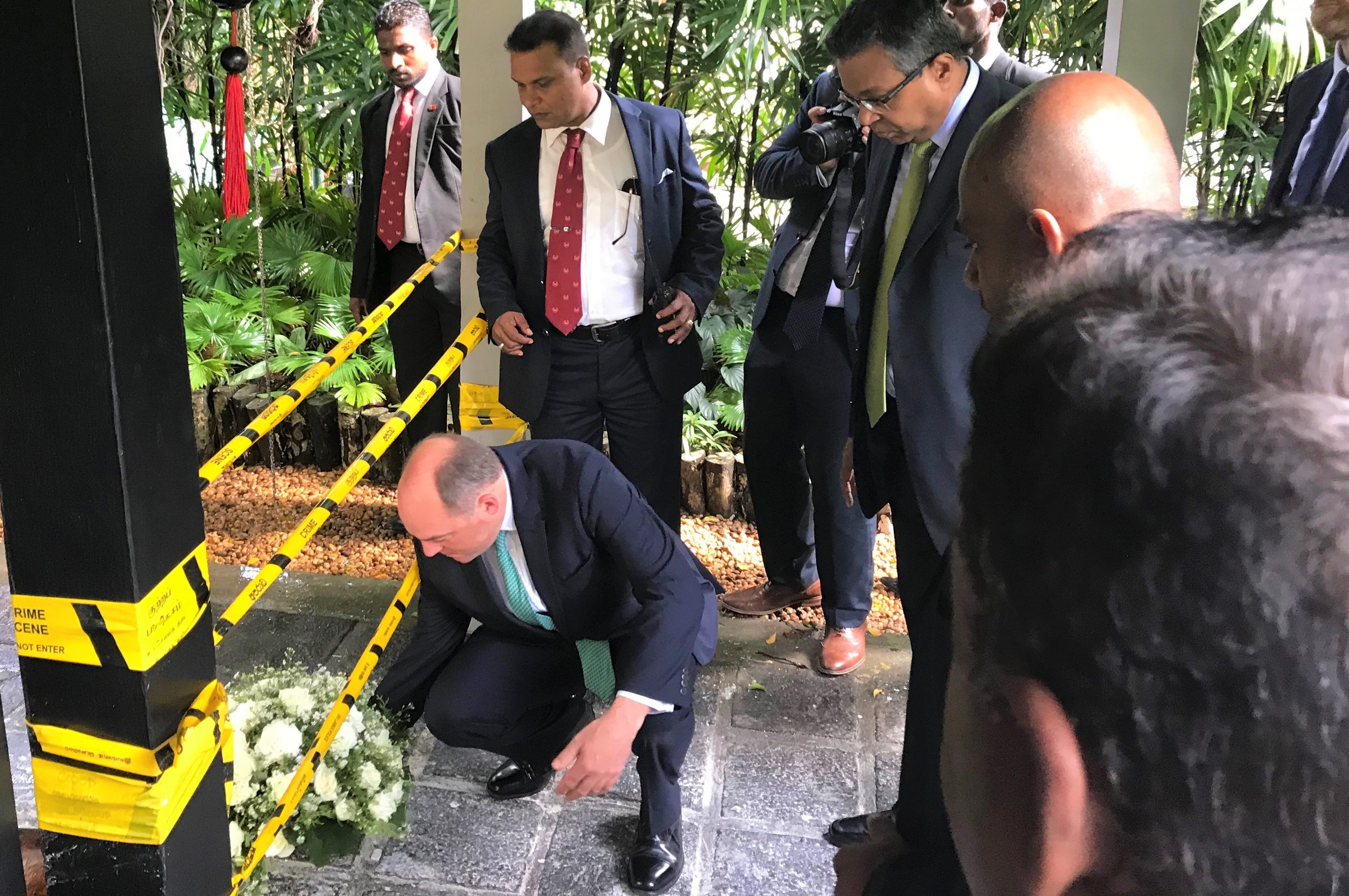 Security Minister, Ben Wallace, lays a wreath on the ground with several people watching.